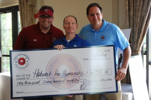 Boomer Foster and Dave Rotell present Peter Larson of Habitat for Humanity (center) with a donation.