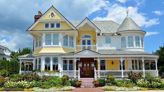 Bright yellow like a sunny day at the beach, this exquisite Victorian home has lush landscaping, a wrap-around front porch and many architectural details. It was lovingly restored, combining old world charm with modern features and technology.