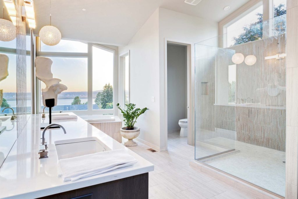 This modern bath has a frameless glass shower enclosure.