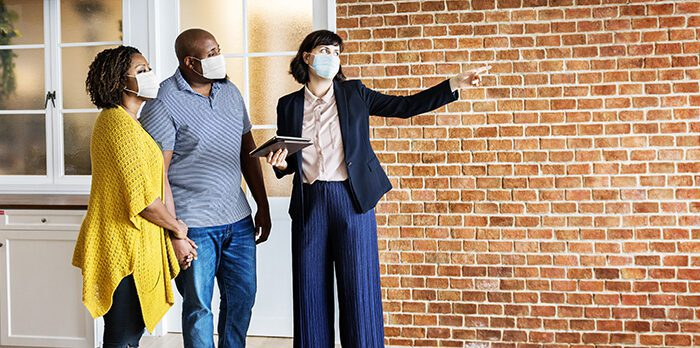 Real estate agent and customer in face mask looking at a home
